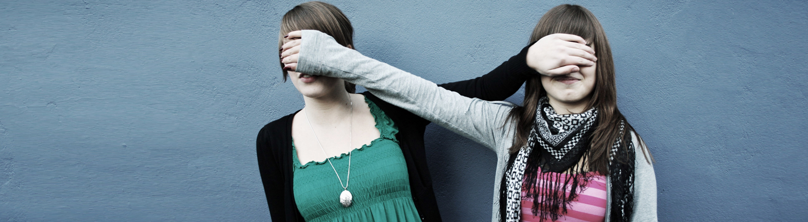 Zwei junge Frauen halten sich gegenseitig die Augen zu.