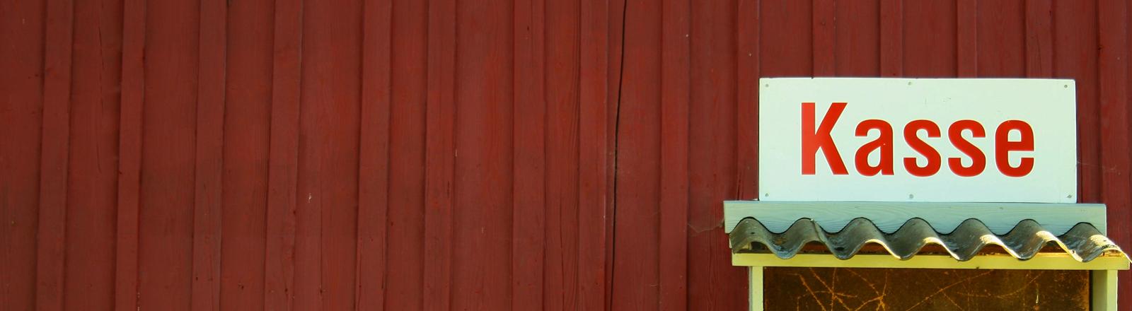 Kassenhäuschen vor roter Wand