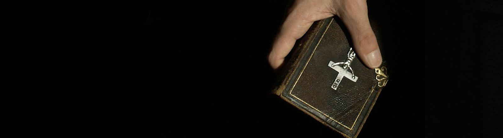 Eine Hand hält eine Bibel.