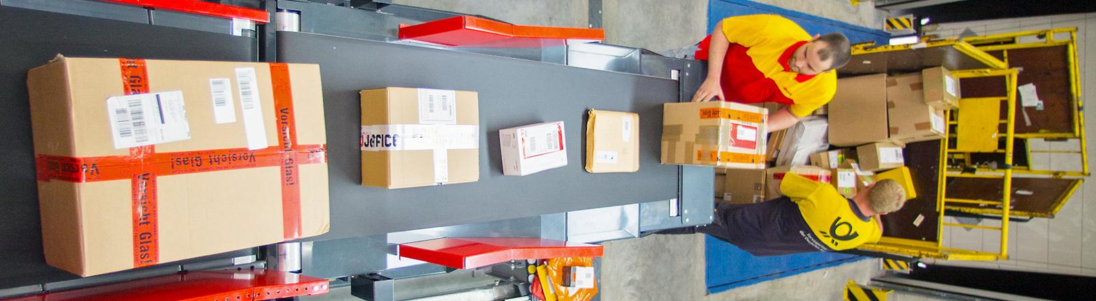 Mitarbeiter des Unternehmens Deutsche Post DHL stellen am 03.07.2013 Pakete auf ein Förderband in der neu eröffneten mechanischen Zustellbasis Berlin.
