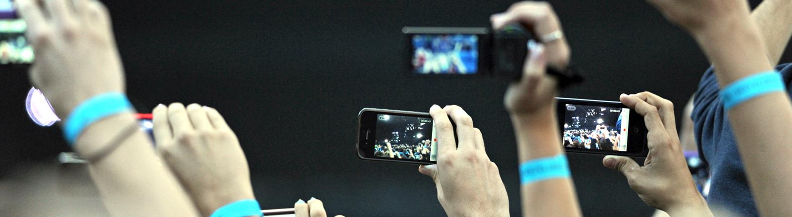 Festivalbesucher filmen am Samstag (21.07.2012) auf dem Königsplatz in München (Oberbayern) mit ihrem Handy den Auftritt von dem französischen DJ Guetta.