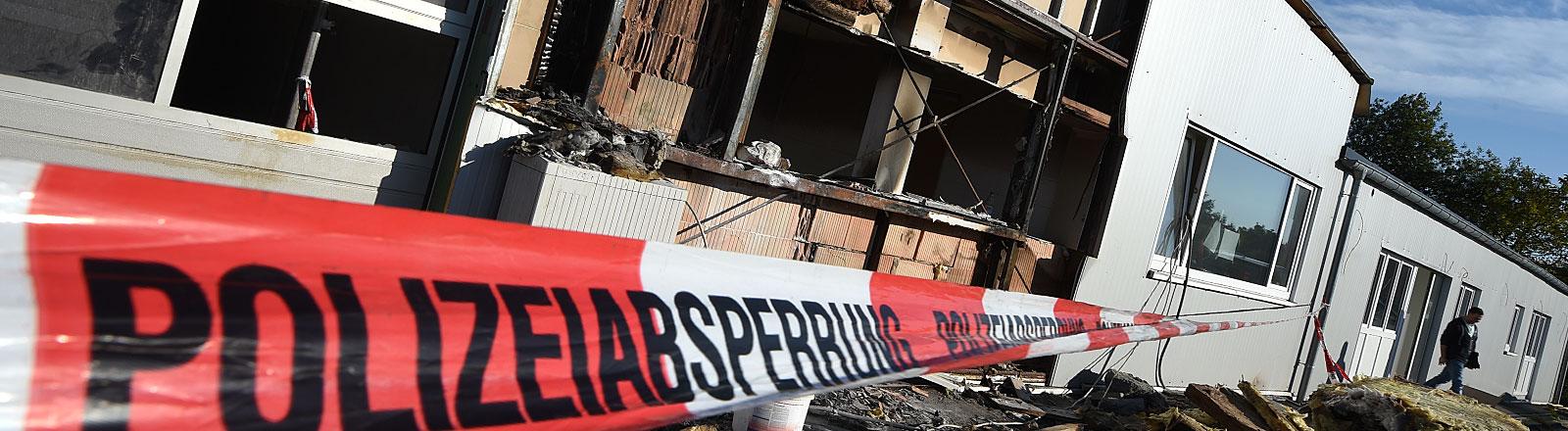 Ein Absperrband der Polizei sichert am 29.09.2015 in Oberteuringen (Baden-Württemberg) eine leerstehende Lagerhalle, deren Fassade am Dienstagmorgen gebrannt hat. Die Lagerhalle sollte zu einer Unterkunft für Asylbewerber umgebaut werden. Die Polizei geht von Brandstiftung aus.