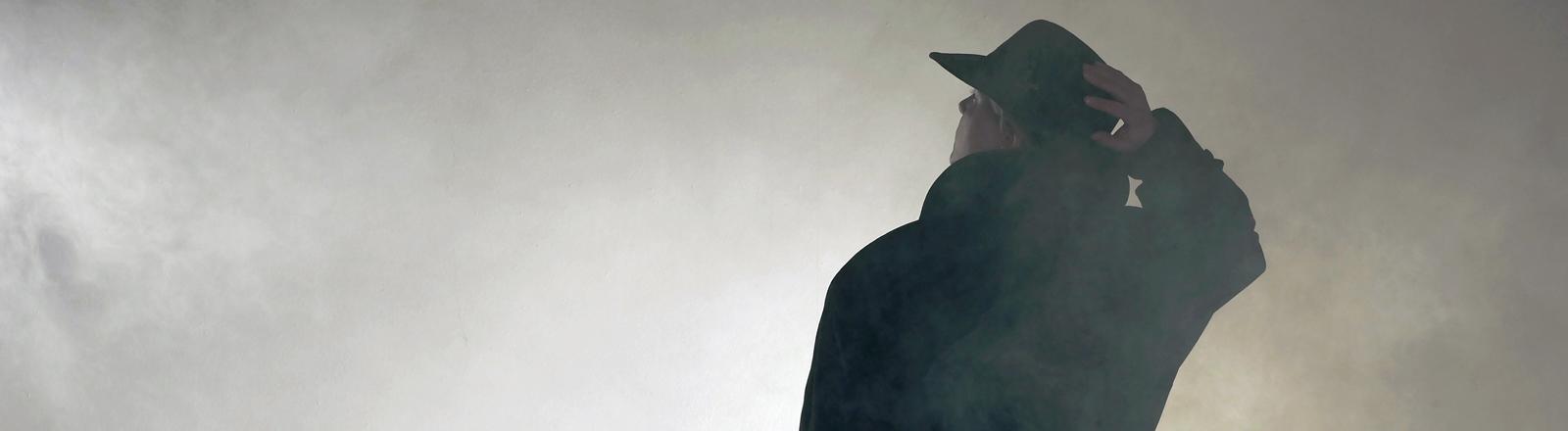 Ein Mann steht im Nebel, Schlapphut, Mantel, das muss ein Agent oder Spion sein!