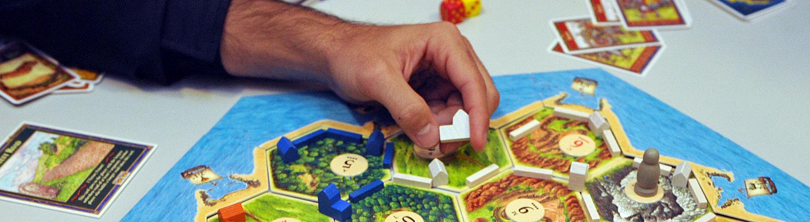 """Eine Hand setzt im Brettspiel """"Die Siedler von Catan"""" einen Spielstein."""