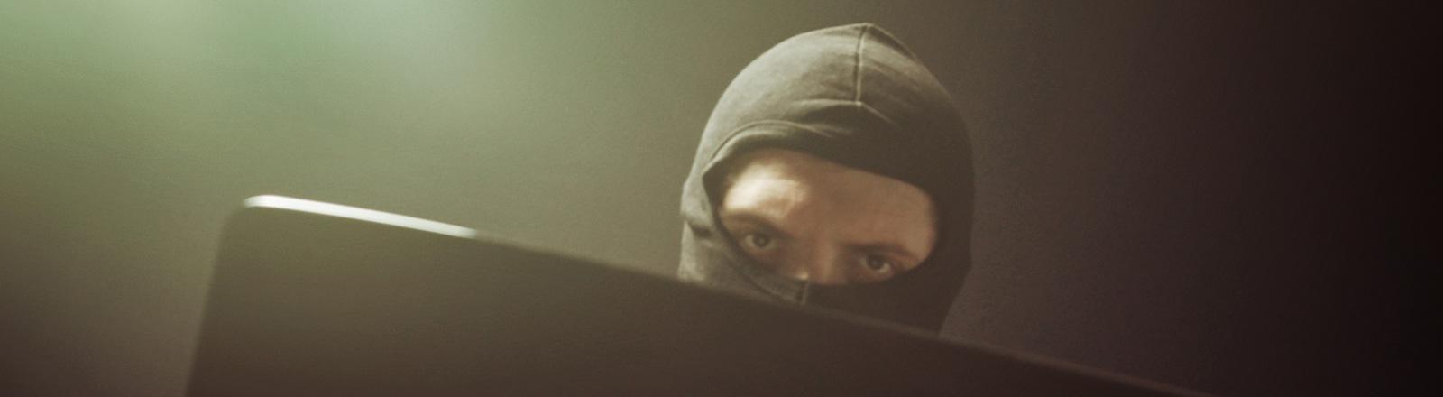 Ein Mann mit schwarzer Ski-Maske schaut über ein Laptop.