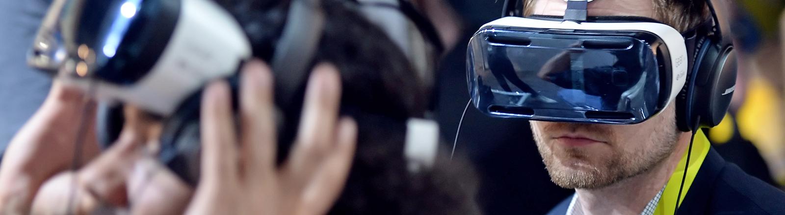"""Messebesucher sehen am 08.01.2015 in Las Vegas, USA, auf der CES (Consumer Electronics Show) durch Samsungs Videobrille """"Oculus VR's Gear VR Headset""""."""