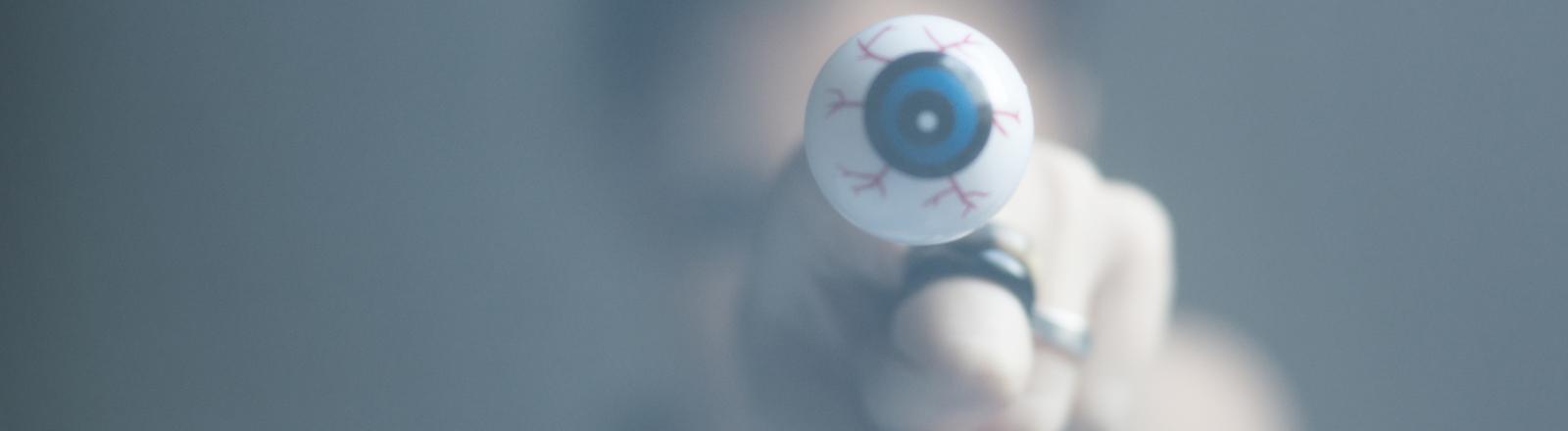 Eine Frau hält einen Ring in Form eines großen Auges vor sich in die Kamera.