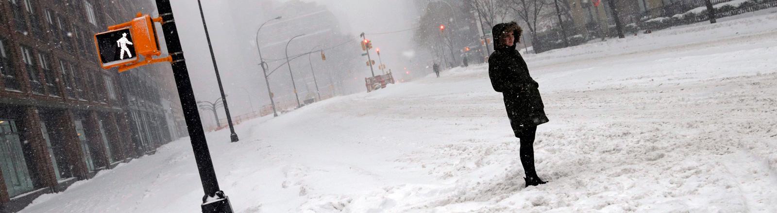 Eine Frau steht alleine auf einer Straße im verschneiten New York City. Es schneit, es fahren keine Autos: Foto: dpa
