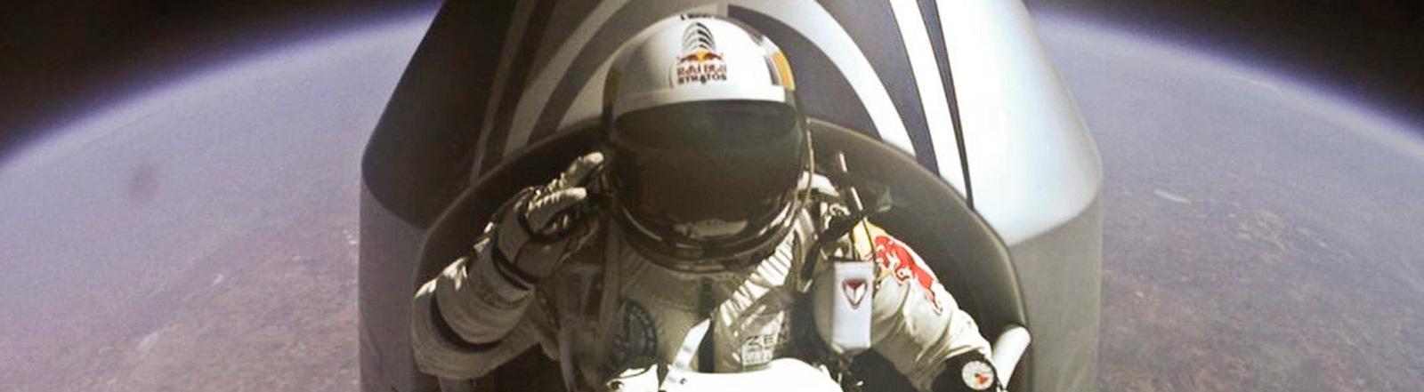 Der Extremsportler Felix Baumgartner steht in einem Anzug in einer Kapsel in knapp 39.000 Metern Höhe. Kurz vor dem Sprung. Unter ihm sieht man die Erde; Foto: dpa