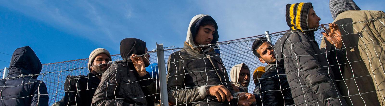 An einem Zaun stehen mehrere Männer. Sie warten an der griechisch-mazedonischen Grenze; Foto: dpa