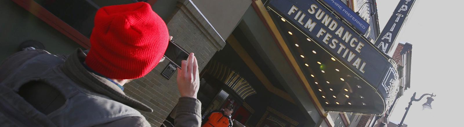 Ein Mann mit roter Wollmütze steht vor einem Kino. Er macht ein Foto mit seinem Smartphone. Über dem Eingang steht Sundance Film Festival; Foto: dpa