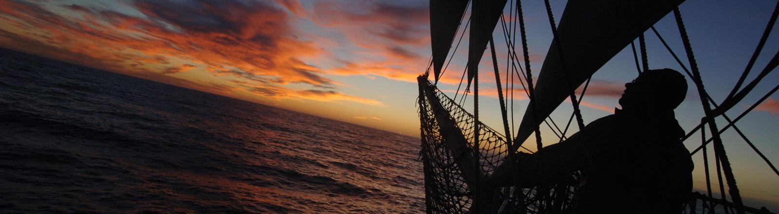 Ein Besatzungsmitglied des Segelschulschiffes Alexander von Humboldt schaut auf dem Weg um Kap Hoorn bei Sonnenuntergang auf das Meer; Foto: dpa