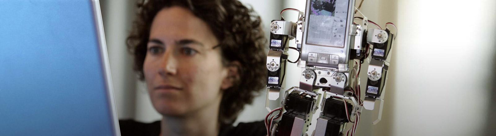 Eine Frau vor einem Computer, der einen Roboter steuert