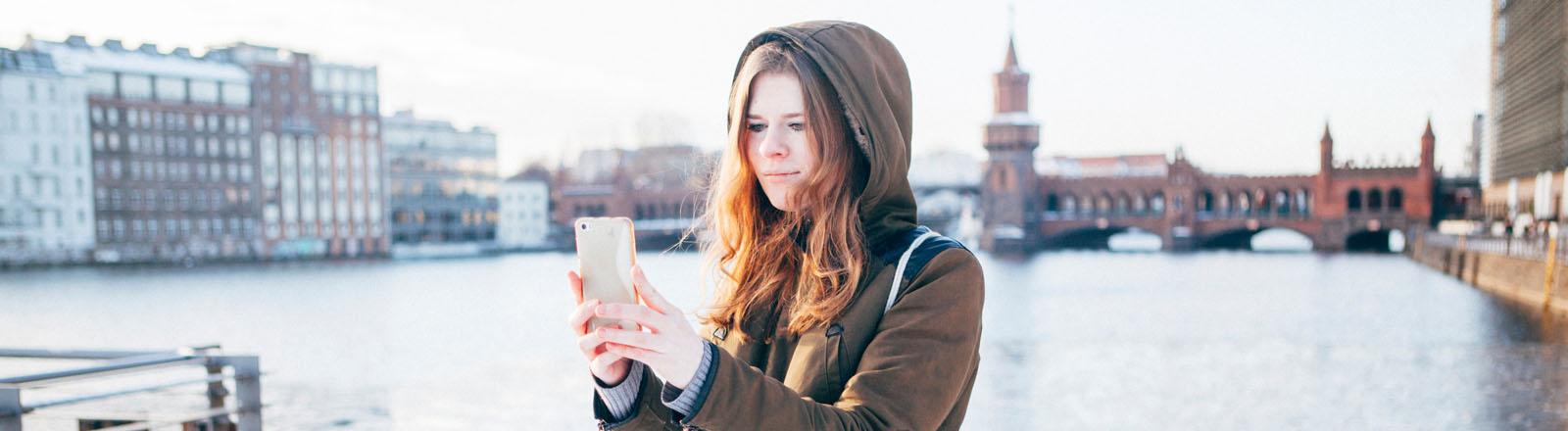 Frau macht Selfie vor Oberbaumbrücke in Berlin
