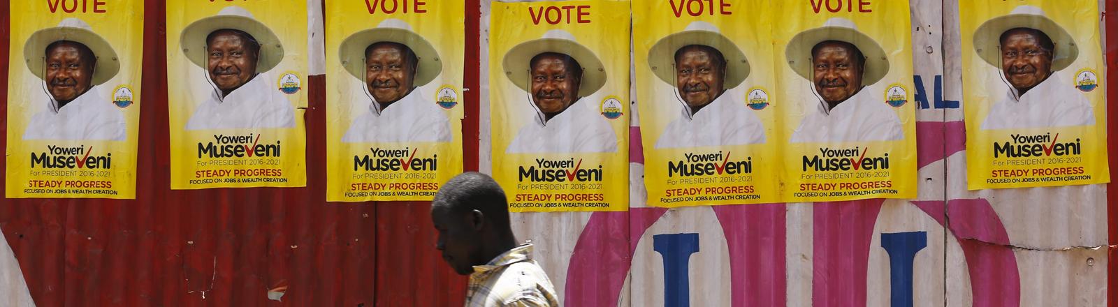Mann läuft entlang einer Mauer mit Wahlplakaten von Museveni