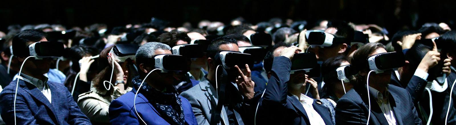 Während der Mobilfunk-Messe in Barcelona präsentiert Samsung ein neues Smartphone. Viele Menschen sitzen in einer Haale und tragen Virtual Reality-Brillen; Foto: dpa