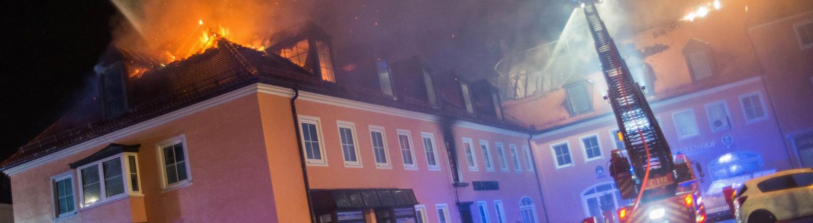 Ein Feuerwehrfahrzeug steht in Bautzen vor einem brennenden Haus. Es ist eine geplanten Flüchtlingsunterkunft (21.02.2016); Foto: dpa