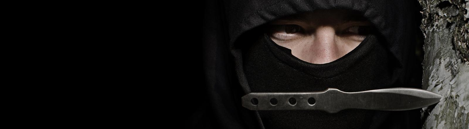 Ein vermummter Mann schaut bedrohlich über ein Messer.
