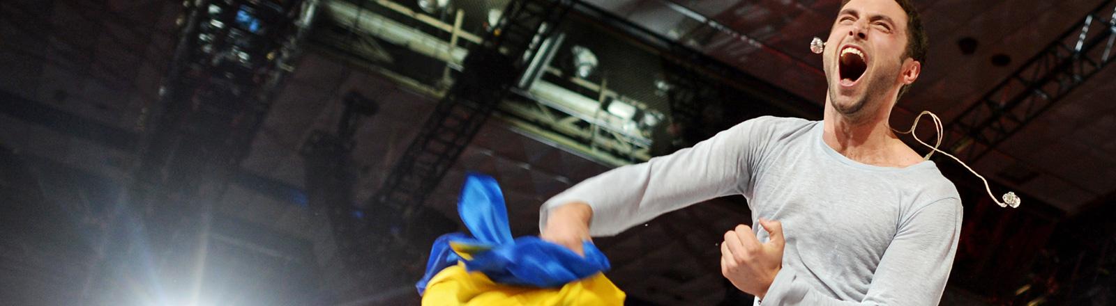 Mans Zelmerlow, der Gewinner des ESC 2015, steht auf der Bühne. Er schreit vor Freude und hat eine Schweden-Flagge in der Hand; Foto: dpa