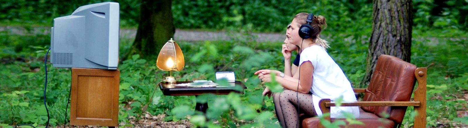 Zwei Frauen sitzen im Wald vor einem Fernseher und schauen in die Röhre.
