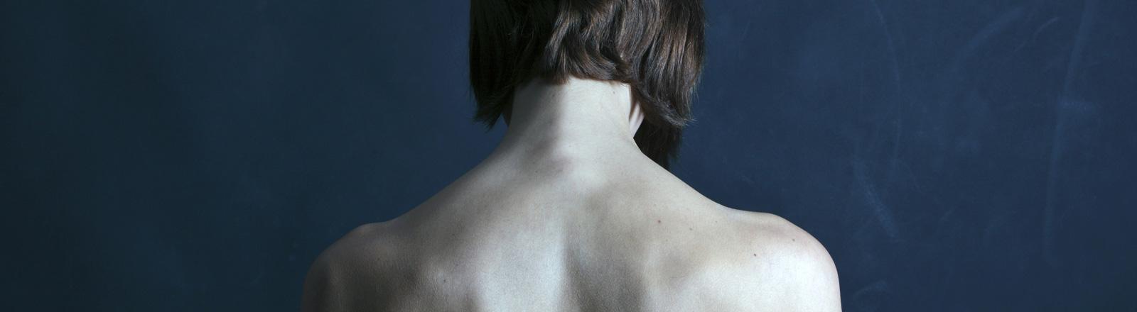 Der Rücken einer Frau mit schulterlangen, braunen Haaren.