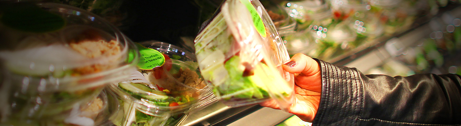 Eine Frau steht vor einem Supermarktregal und hält eine Schüssel mit Salat in der Hand; Foto: dpa