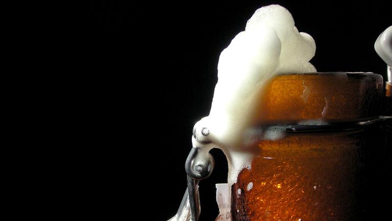 Aus einer Flasche Bier sprudelt der Schaum.