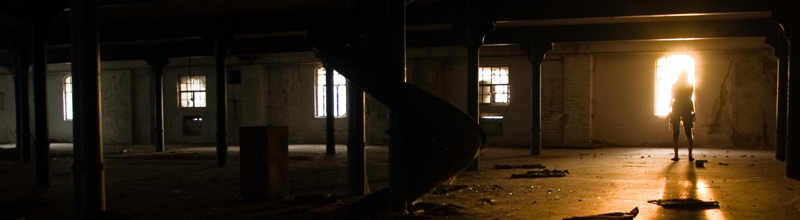 Eine Frau steht in einer düsteren Fabrikhalle.