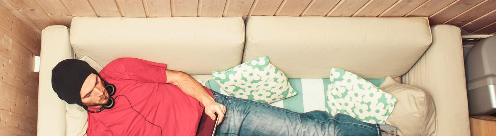 Typ mit Tablet auf dem Sofa