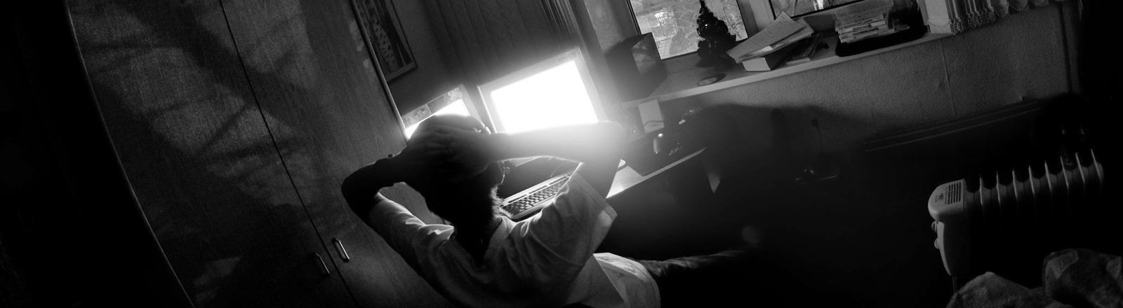 Schwarz-Weiß-Foto: In einem Zimmer sitzt ein junger Mann vor zwei leuchtenden Bildschirmen.