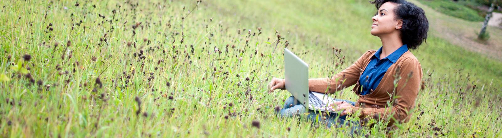 Eine Frau sitzt auf einer Wiese und arbeitet am Notebook.
