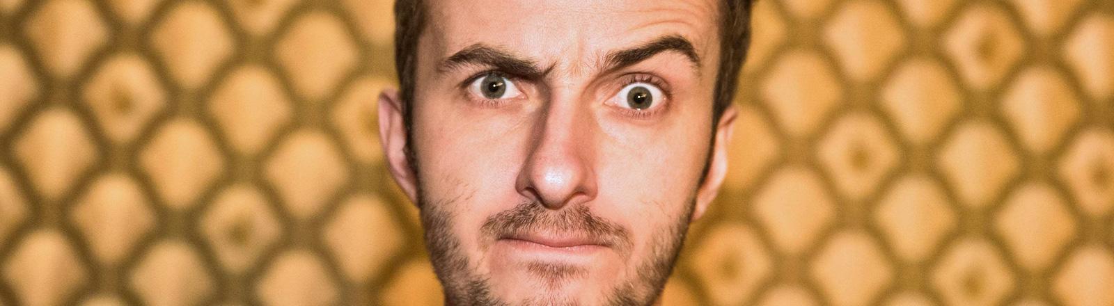 Der Satiriker Jan Böhmermann steht vor einer gelben Tapete mit Muster. Er zieht die linke Augenbraue nach oben.