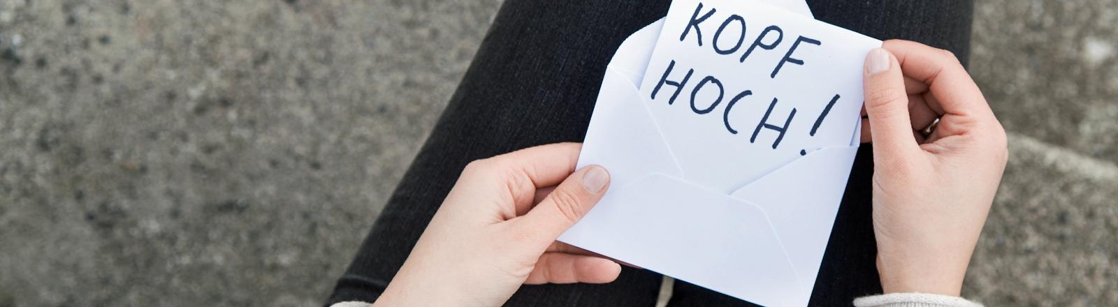 """Eine Frau hält einen Zettel in den Händen: """"Kopf hoch""""."""