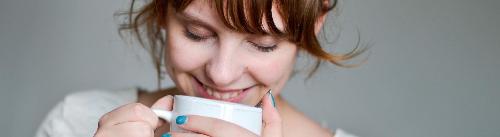 Eine Frau hält eine Kaffeetasse in den Händen. Sie hat die Augen geschlossen und lächelt.