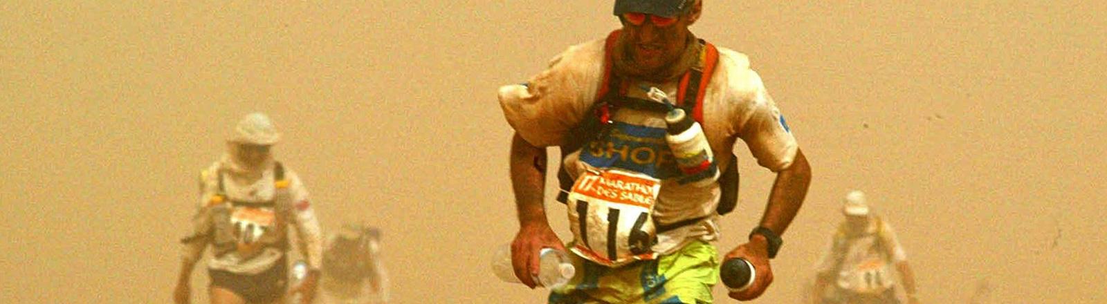 Ein Mann läuft durch die Sahara. Hinter ihm sind weitere Läufer zu erkennen; Foto: dpa