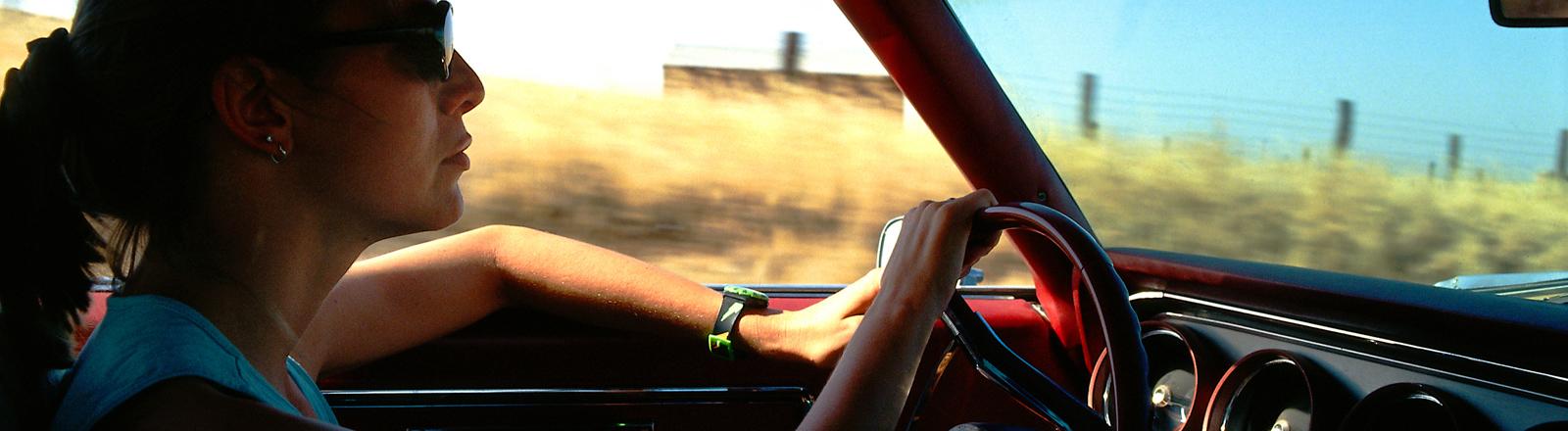 Frau sitzt am Steuer eines Autos.