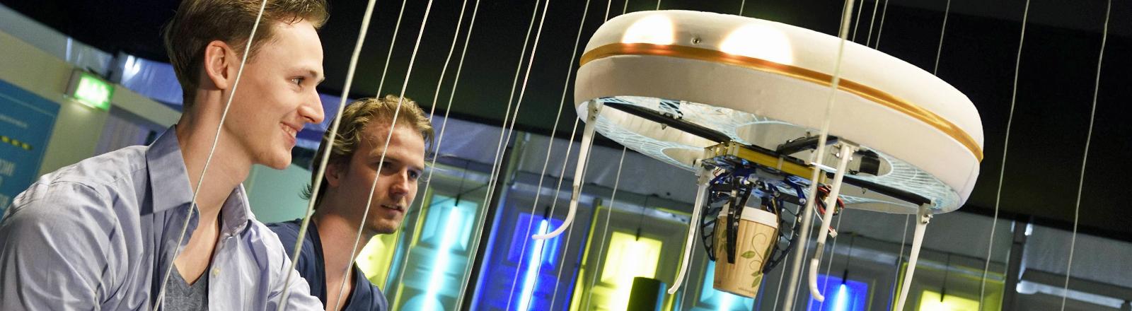 Zwei junge Männer bekommen ihren Kaffee von einer Drohne in Eindhoven serviert.