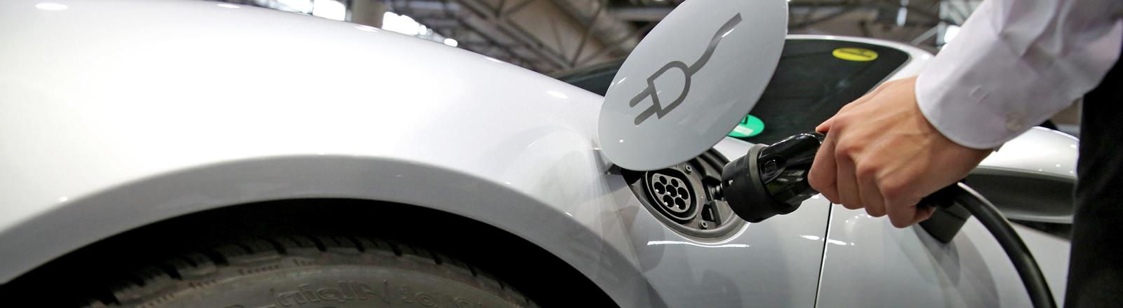 Der Prototyp eines Porsche Boxster E wird am 14.04.2016 auf einer Konferenz zu Elektromobilität in Leipzig (Sachsen) mit Hilfe eines Ladekabels aufgeladen