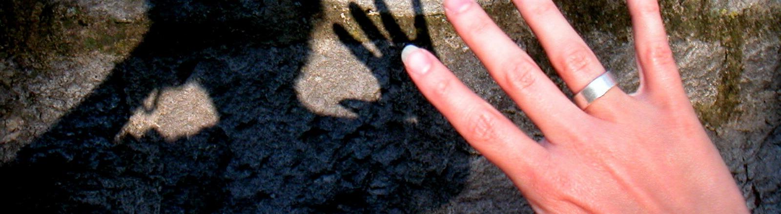 Eine Frau hält abwehrend ihre Hand hoch und wirft einen Schatten auf eine Mauer.