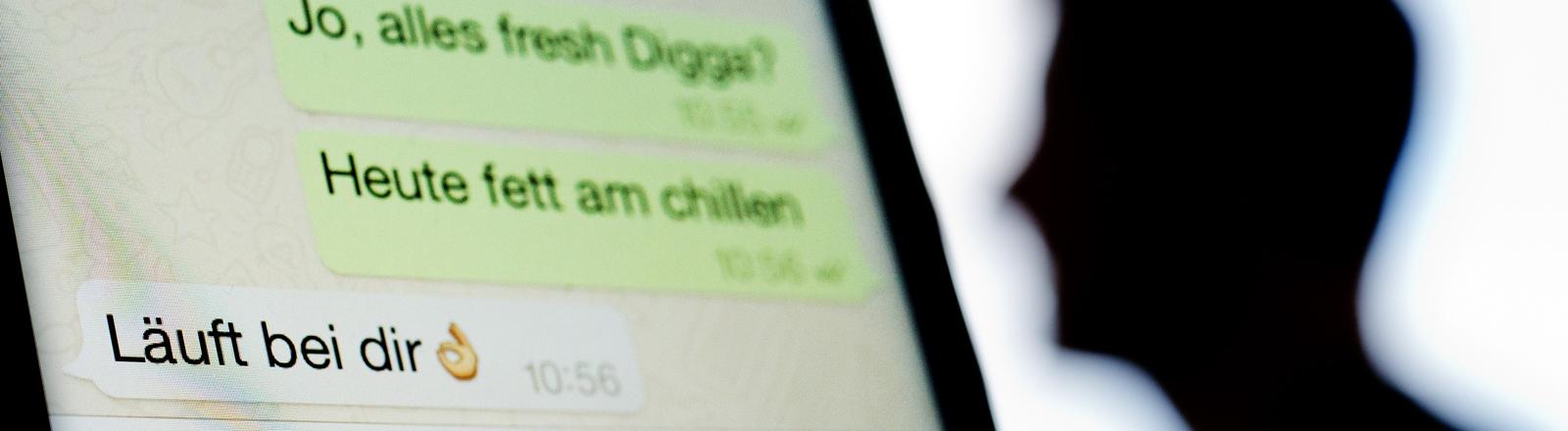 Display eines Smartphones zeigt einen Chat an. Daneben die Silhouette eines Mannes.