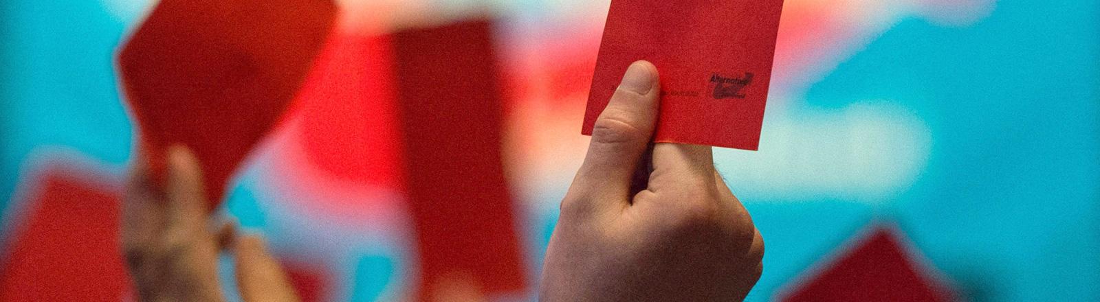 Beim Parteitag der AfD werden rote Stimmkarten in die Höhe gehalten (01.05.2016); Foto: dpa