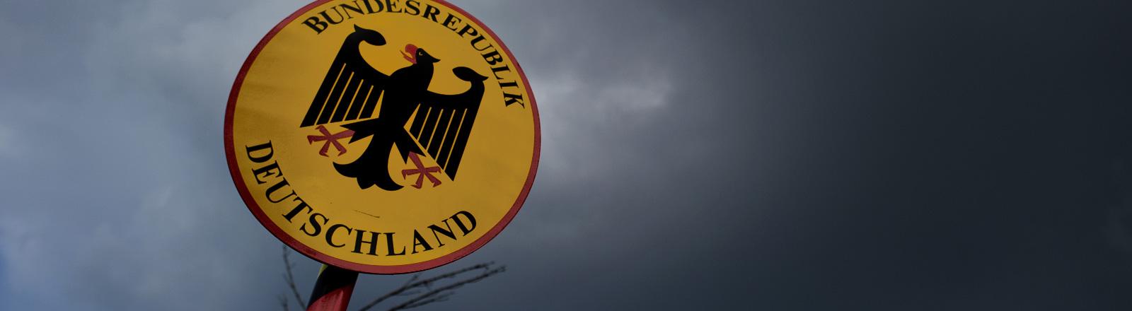"""Dunkle Wolken ziehen über ein Grenzschild, darauf ist der Bundesadler abgebildet und es ist """"Bundesrepublik Deutschland"""" zu lesen; Foto: dpa"""