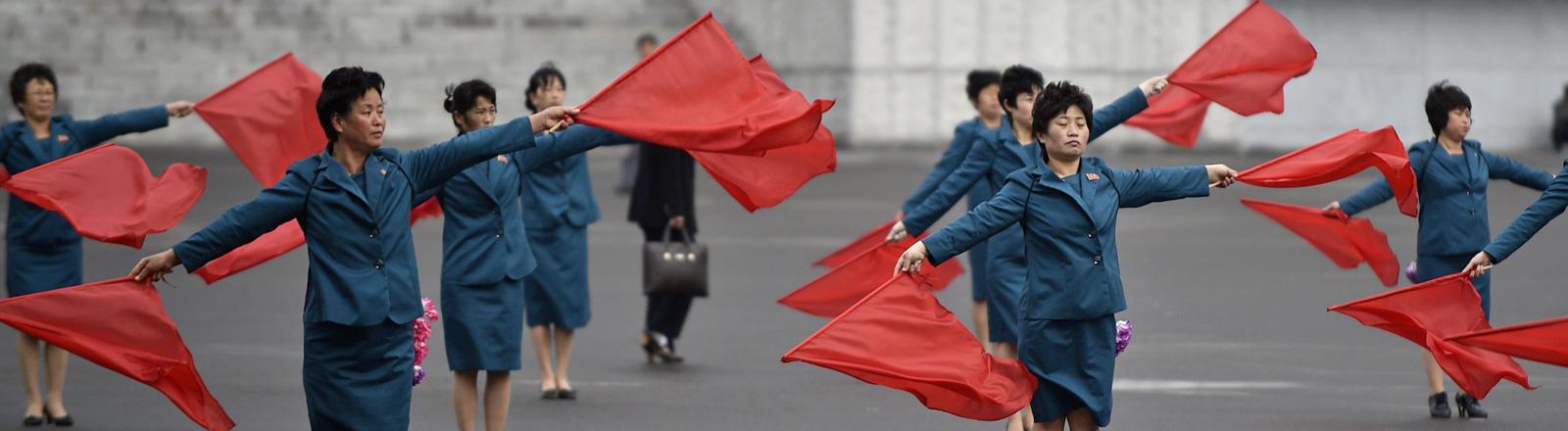 Auf einem Platz stehen Frauen in blauen Röcken und Bläzern. Sie halten in jeder Hand eine rote Fahne mit der sie winken. Pjöngjang am 6. Mai 2016; Foto: dpa