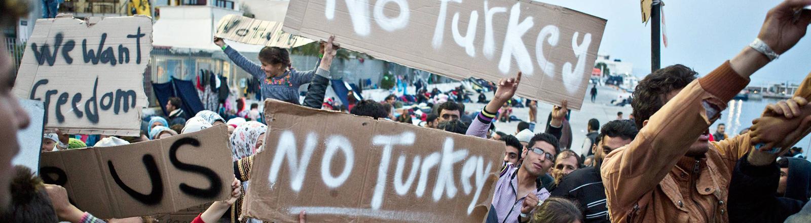 """Flüchtlinge protestieren im Hafen der griechischen Insel Chios. Sie halten Papierschilder in die Höhe, darauf steht """"No Turkey"""" (3. April 2016)."""