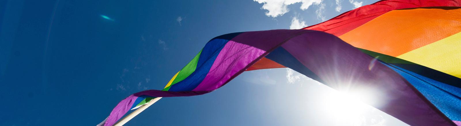 Eine Regenbogenfahne weht im Wind, blauer Himmel und Sonnenschein; Foto: dpa