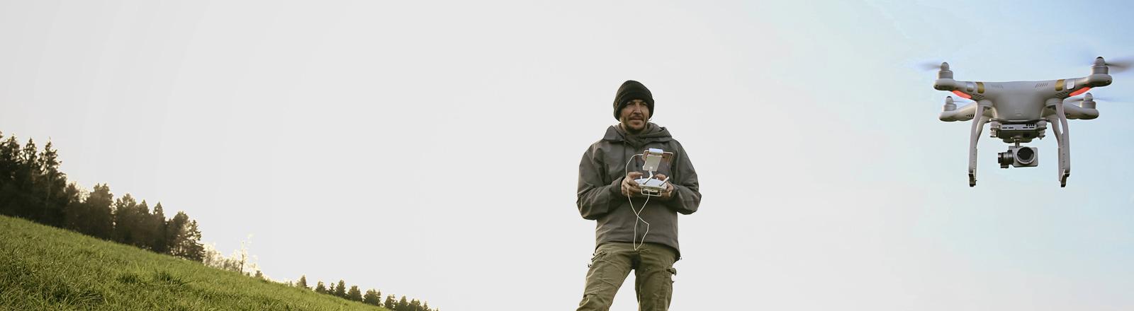 Ein Mann steht auf einer Wiese, er steuert eine Drohne. Der Mann trägt eine dicke Jacke und Mütze.
