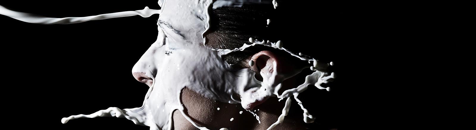Im Profil ist ein junger Mann zu sehen vor schwarzem Hintergrund. Von links bekommt er Milch ins Gesicht geschüttet.