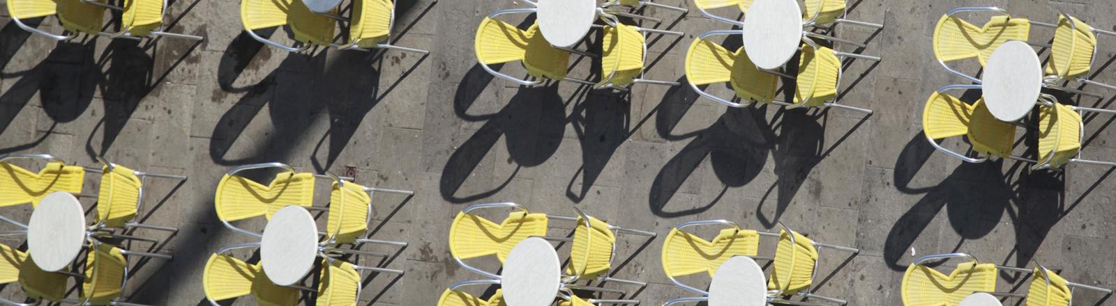 Blick aus der Vogelperspektive: Auf einem Platz stehen runde Tische mit jeweils vier Stühlen. Alle sind leer.