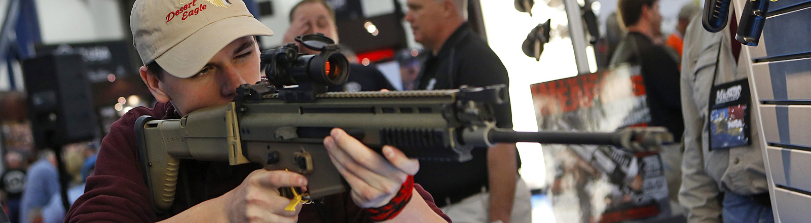 Ein junger Mann hält eine Waffe in der Hand und zielt. Jahrestreffen der US-Waffenlobby 2013; Foto: dpa