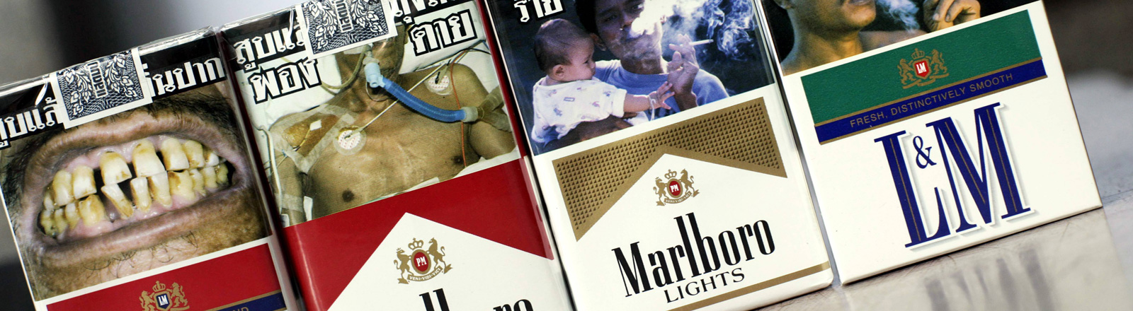 Auf vier Zigarettenpackungen sind Schockfotos. Zum Beispiel von verfaulten Zähnen und einer Frau, die raucht und ein kleines Kind auf dem Arm hält.